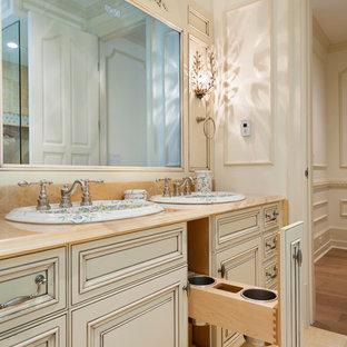 Diseño de cuarto de baño principal, clásico, con lavabo encastrado, armarios con paneles con relieve, puertas de armario con efecto envejecido, encimera de ónix, bañera con patas, ducha esquinera, sanitario de dos piezas, baldosas y/o azulejos amarillos, baldosas y/o azulejos de piedra, paredes blancas y suelo de mármol
