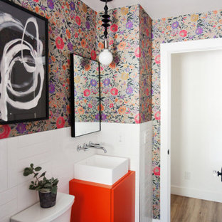 Example of a small eclectic 3/4 white tile and ceramic tile ceramic floor, black floor, single-sink and wallpaper bathroom design in Phoenix with flat-panel cabinets, orange cabinets, multicolored walls, a vessel sink, laminate countertops, orange countertops and a freestanding vanity