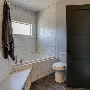 グランドラピッズの広いコンテンポラリースタイルのおしゃれなマスターバスルーム (シェーカースタイル扉のキャビネット、ヴィンテージ仕上げキャビネット、ドロップイン型浴槽、コーナー設置型シャワー、分離型トイレ、白いタイル、サブウェイタイル、グレーの壁、磁器タイルの床、ベッセル式洗面器、珪岩の洗面台、黒い床、開き戸のシャワー、白い洗面カウンター) の写真