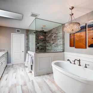 Modelo de cuarto de baño principal, tradicional renovado, grande, con armarios con paneles con relieve, puertas de armario blancas, bañera exenta, baldosas y/o azulejos grises, baldosas y/o azulejos de porcelana, paredes grises, suelo de baldosas de porcelana, lavabo bajoencimera, encimera de granito, ducha esquinera y ducha con puerta con bisagras