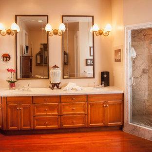 Immagine di una stanza da bagno padronale chic di medie dimensioni con ante con riquadro incassato, ante in legno bruno, doccia ad angolo, piastrelle grigie, piastrelle di marmo, pareti beige, parquet scuro, lavabo sottopiano, top in granito, pavimento rosso e porta doccia a battente
