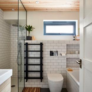 Foto på ett litet badrum med dusch, med ett platsbyggt badkar, en hörndusch, en toalettstol med hel cisternkåpa, vit kakel, keramikplattor, ett avlångt handfat, grått golv och med dusch som är öppen