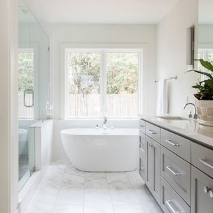 Mid-sized transitional master white floor bathroom photo in Sacramento with shaker cabinets, gray cabinets, white walls, an undermount sink, a hinged shower door and white countertops