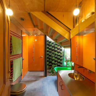 Modelo de cuarto de baño urbano con lavabo integrado, armarios con paneles lisos, puertas de armario de madera oscura, bañera exenta, ducha abierta, baldosas y/o azulejos naranja, parades naranjas y ducha abierta