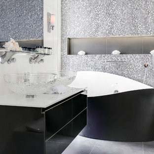 Design ideas for a contemporary ensuite bathroom in London with flat-panel cabinets, a freestanding bath, mosaic tiles, a vessel sink, grey floors, black cabinets and multi-coloured tiles.