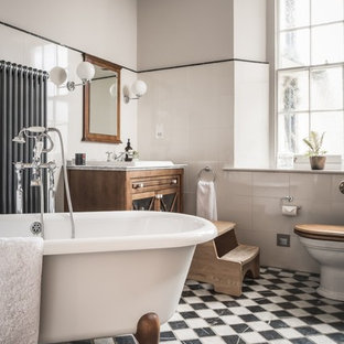 Foto di una stanza da bagno padronale classica con ante di vetro, ante in legno scuro, vasca con piedi a zampa di leone, piastrelle bianche, pareti grigie, lavabo da incasso e pavimento multicolore