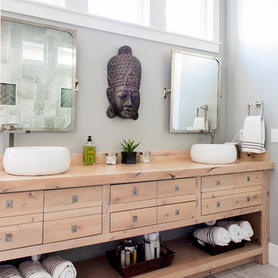 Inspiration for a mid-sized master gray tile and porcelain tile porcelain tile and gray floor doorless shower remodel in Birmingham with gray walls, flat-panel cabinets, light wood cabinets, a vessel sink, a one-piece toilet, wood countertops and brown countertops