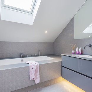 Design ideas for a contemporary bathroom in London with flat-panel cabinets, grey cabinets, grey tiles, grey walls, a submerged sink and a submerged bath.