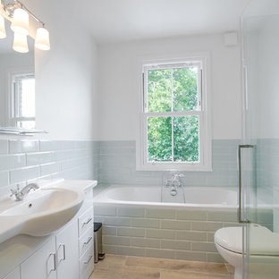 Small classic family bathroom in London with flat-panel cabinets, white cabinets, a built-in bath, grey tiles, ceramic tiles, white walls, porcelain flooring, brown floors, a hinged door and a console sink.