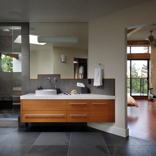 Trendy black tile alcove shower photo in Vancouver with a vessel sink, flat-panel cabinets and medium tone wood cabinets