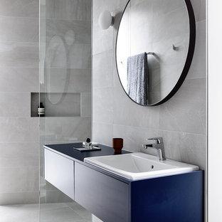 Immagine di una grande stanza da bagno minimal con ante lisce, ante blu, doccia alcova, WC sospeso, piastrelle grigie, piastrelle in ceramica, pareti grigie, pavimento con piastrelle in ceramica, lavabo da incasso, top in laminato, pavimento grigio, doccia aperta e top blu