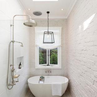 メルボルンのコンテンポラリースタイルのおしゃれな浴室 (白いタイル、白い壁、磁器タイルの床、ベージュの床、レンガ壁) の写真