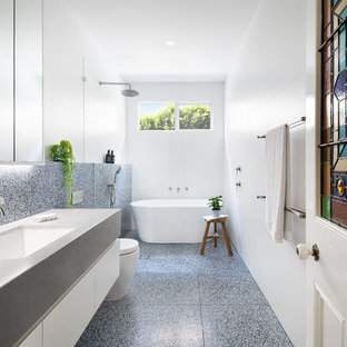This is an example of a contemporary bathroom in Melbourne with flat-panel cabinets, white cabinets, a freestanding tub, a curbless shower, black and white tile, white tile, white walls, an undermount sink, black floor, an open shower and grey benchtops.