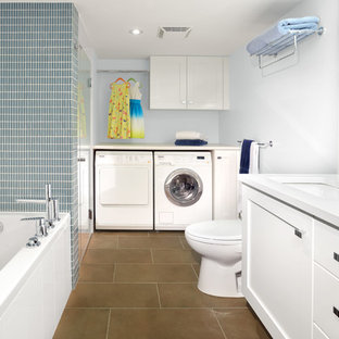 Diseño de cuarto de baño actual con lavabo bajoencimera, armarios con paneles lisos, puertas de armario blancas y baldosas y/o azulejos grises