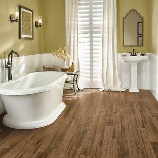 Imagen de cuarto de baño con ducha, tradicional, de tamaño medio, con bañera exenta, paredes amarillas, suelo vinílico y lavabo con pedestal