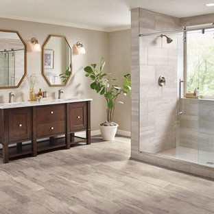 Idée de décoration pour une grand douche en alcôve principale tradition avec un placard à porte shaker, des portes de placard en bois sombre, un carrelage gris, des carreaux de porcelaine, un mur beige, un sol en vinyl, un lavabo encastré, un plan de toilette en verre recyclé, un sol beige et une cabine de douche à porte battante.