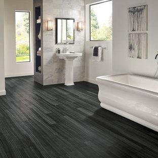 Imagen de cuarto de baño principal, contemporáneo, grande, con bañera exenta, paredes blancas, suelo vinílico y lavabo con pedestal