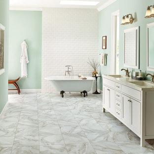 На фото: с высоким бюджетом большие главные ванные комнаты в морском стиле с фасадами в стиле шейкер, белыми фасадами, ванной на ножках, бежевой плиткой, серой плиткой, белой плиткой, каменной плиткой, синими стенами, мраморным полом, монолитной раковиной и столешницей из гранита