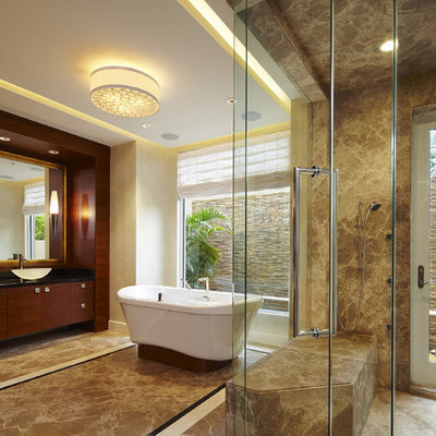 Example of a large trendy master brown tile and marble tile marble floor bathroom design in Miami with a vessel sink, dark wood cabinets, a one-piece toilet, beige walls, granite countertops and flat-panel cabinets