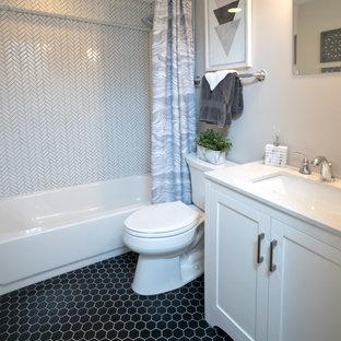 Foto på ett litet funkis vit badrum, med luckor med infälld panel, vita skåp, en toalettstol med separat cisternkåpa, vit kakel, vita väggar, klinkergolv i keramik, ett undermonterad handfat, bänkskiva i kvarts, svart golv, ett badkar i en alkov och en dusch/badkar-kombination