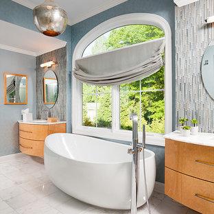 Immagine di una grande stanza da bagno padronale minimal con ante lisce, ante in legno chiaro, vasca freestanding, doccia alcova, piastrelle blu, piastrelle di vetro, pareti blu, pavimento in marmo, lavabo sottopiano, top in marmo, pavimento bianco, porta doccia a battente e top turchese