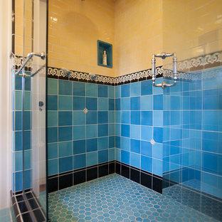 Modelo de cuarto de baño principal, grande, con ducha doble, sanitario de dos piezas, baldosas y/o azulejos azules, baldosas y/o azulejos de porcelana, paredes amarillas, suelo de baldosas de porcelana y lavabo con pedestal