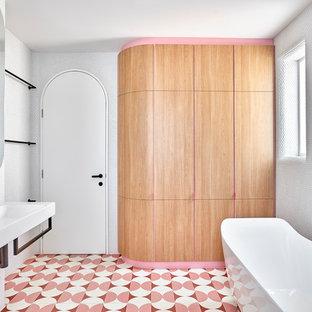 Удачное сочетание для дизайна помещения: маленькая главная ванная комната в скандинавском стиле с отдельно стоящей ванной, угловым душем, унитазом-моноблоком, белой плиткой, плиткой мозаикой, белыми стенами, полом из цементной плитки, подвесной раковиной, розовым полом и душем с распашными дверями - самое интересное для вас