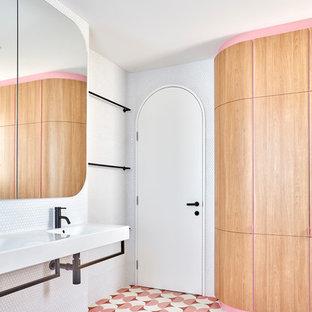 Foto de cuarto de baño principal, nórdico, pequeño, con bañera exenta, ducha esquinera, sanitario de una pieza, baldosas y/o azulejos blancos, baldosas y/o azulejos en mosaico, paredes blancas, suelo de azulejos de cemento, lavabo suspendido, suelo rosa y ducha con puerta con bisagras