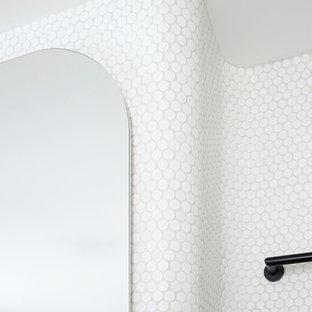 Inredning av ett skandinaviskt litet en-suite badrum, med ett fristående badkar, en hörndusch, en toalettstol med hel cisternkåpa, vit kakel, mosaik, vita väggar, cementgolv, ett väggmonterat handfat, rosa golv och dusch med gångjärnsdörr
