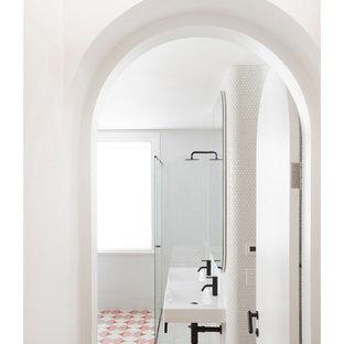 Inredning av ett minimalistiskt litet en-suite badrum, med ett fristående badkar, en hörndusch, en toalettstol med hel cisternkåpa, vit kakel, mosaik, vita väggar, cementgolv, ett väggmonterat handfat, rosa golv och dusch med gångjärnsdörr