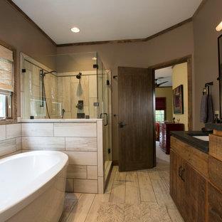 На фото: главная ванная комната среднего размера в стиле рустика с плоскими фасадами, темными деревянными фасадами, отдельно стоящей ванной, угловым душем, раздельным унитазом, бежевой плиткой, коричневыми стенами, полом из винила, врезной раковиной, столешницей из талькохлорита, бежевым полом и душем с распашными дверями