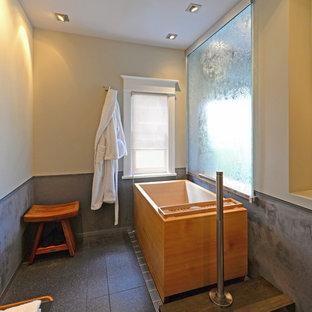 Modelo de cuarto de baño con ducha, asiático, pequeño, con lavabo sobreencimera, armarios tipo mueble, puertas de armario de madera en tonos medios, encimera de granito, bañera japonesa, sanitario de pared, baldosas y/o azulejos negros, baldosas y/o azulejos de porcelana, paredes grises y suelo de baldosas de porcelana
