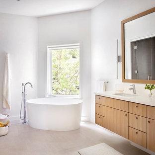 Ispirazione per una stanza da bagno padronale nordica con ante lisce, ante in legno chiaro, vasca freestanding, pareti grigie, lavabo sottopiano, pavimento beige e top beige