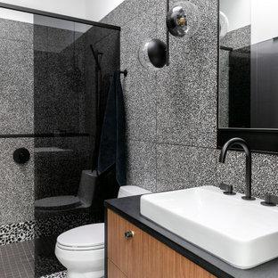 Aménagement d'une petit douche en alcôve principale contemporaine avec un placard à porte plane, un WC à poser, un carrelage noir et blanc, des carreaux de porcelaine, un mur blanc, une vasque, un plan de toilette en granite, un sol noir, une cabine de douche à porte battante, un plan de toilette noir, meuble simple vasque, meuble-lavabo suspendu, des portes de placard en bois brun et un sol en terrazzo.