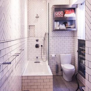 Imagen de cuarto de baño principal, urbano, pequeño, con lavabo suspendido, armarios tipo vitrina, puertas de armario grises, bañera encastrada, ducha esquinera, baldosas y/o azulejos blancos, paredes blancas, suelo de baldosas de porcelana, baldosas y/o azulejos de cemento, suelo marrón y sanitario de una pieza