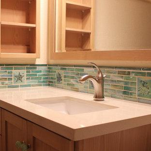 Immagine di una stanza da bagno costiera di medie dimensioni con lavabo sottopiano, ante in stile shaker, ante in legno chiaro, top in quarzo composito, vasca/doccia, piastrelle di vetro e pareti beige