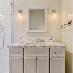 サンフランシスコの小さいトラディショナルスタイルのおしゃれなバスルーム (浴槽なし) (インセット扉のキャビネット、白いキャビネット、アルコーブ型シャワー、白いタイル、サブウェイタイル、白い壁、セラミックタイルの床、アンダーカウンター洗面器、珪岩の洗面台、白い床、開き戸のシャワー) の写真