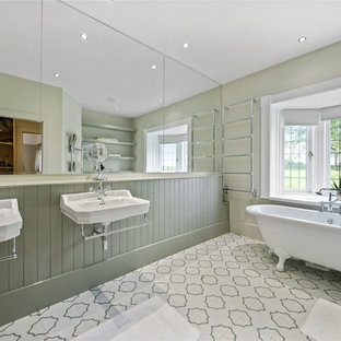 This is an example of a classic ensuite bathroom in Surrey with a claw-foot bath, green walls, a wall-mounted sink and multi-coloured floors.