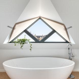Bild på ett mellanstort funkis badrum, med ett fristående badkar, vita väggar, korkgolv och brunt golv