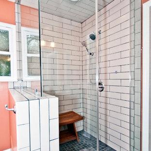 Diseño de cuarto de baño principal, urbano, de tamaño medio, con lavabo bajoencimera, armarios con paneles con relieve, puertas de armario de madera en tonos medios, encimera de granito, bañera exenta, ducha esquinera, sanitario de dos piezas, baldosas y/o azulejos grises, baldosas y/o azulejos de cerámica, parades naranjas y suelo de baldosas de porcelana