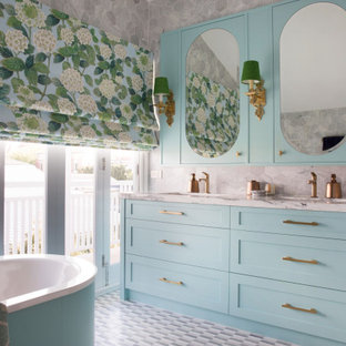 Design ideas for a beach style bathroom in Other with shaker cabinets, blue cabinets, a freestanding tub, gray tile, an undermount sink, grey floor, white benchtops, a double vanity and a built-in vanity.