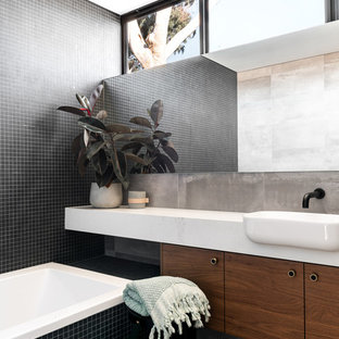 This is an example of a mid-sized contemporary kids bathroom in Perth with medium wood cabinets, a drop-in tub, black tile, porcelain tile, black walls, porcelain floors, engineered quartz benchtops, grey floor, white benchtops and a drop-in sink.