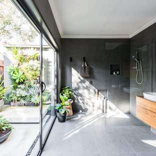Contemporary bathroom in Melbourne with medium wood cabinets, an alcove shower, gray tile, grey walls, a vessel sink, wood benchtops, grey floor, an open shower and brown benchtops.