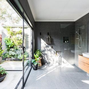 Großes Modernes Badezimmer En Suite mit flächenbündigen Schrankfronten, braunen Schränken, bodengleicher Dusche, grauen Fliesen, grauer Wandfarbe, Aufsatzwaschbecken, Waschtisch aus Holz, grauem Boden, offener Dusche und brauner Waschtischplatte in Melbourne