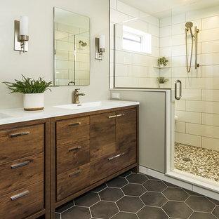 ミネアポリスの中サイズのトランジショナルスタイルのおしゃれなマスターバスルーム (濃色木目調キャビネット、白いタイル、サブウェイタイル、グレーの壁、磁器タイルの床、アンダーカウンター洗面器、珪岩の洗面台、グレーの床、開き戸のシャワー、白い洗面カウンター、家具調キャビネット) の写真