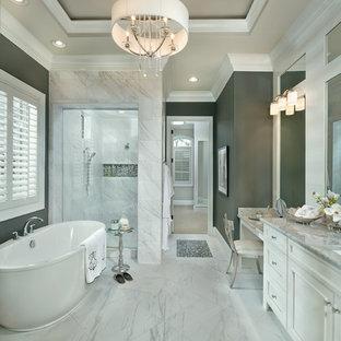 シンシナティの広いトランジショナルスタイルのおしゃれなマスターバスルーム (アンダーカウンター洗面器、落し込みパネル扉のキャビネット、白いキャビネット、大理石の洗面台、置き型浴槽、アルコーブ型シャワー、白いタイル、グレーの壁、磁器タイル、磁器タイルの床、白い床) の写真