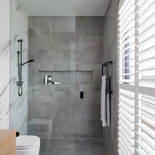 Contemporary bathroom in Other with flat-panel cabinets, medium wood cabinets, a curbless shower, a wall-mount toilet, gray tile, white tile, white walls, wood benchtops, grey floor, an open shower and brown benchtops.