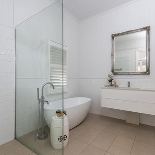 Inspiration for a beach style bathroom in Townsville with flat-panel cabinets, white cabinets, a freestanding tub, a corner shower, white tile, white walls, an undermount sink, grey floor, an open shower and white benchtops.