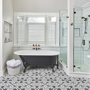 シャーロットの中くらいのトランジショナルスタイルのおしゃれなマスターバスルーム (猫足バスタブ、コーナー設置型シャワー、白いタイル、セラミックタイル、白い壁、セメントタイルの床、マルチカラーの床、開き戸のシャワー) の写真