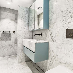 Photo of a mid-sized contemporary master bathroom in Sydney with blue cabinets, a wall-mount toilet, gray tile, white tile, marble, grey walls, marble floors, an undermount sink, marble benchtops, grey floor, an open shower, flat-panel cabinets, a curbless shower and white benchtops.
